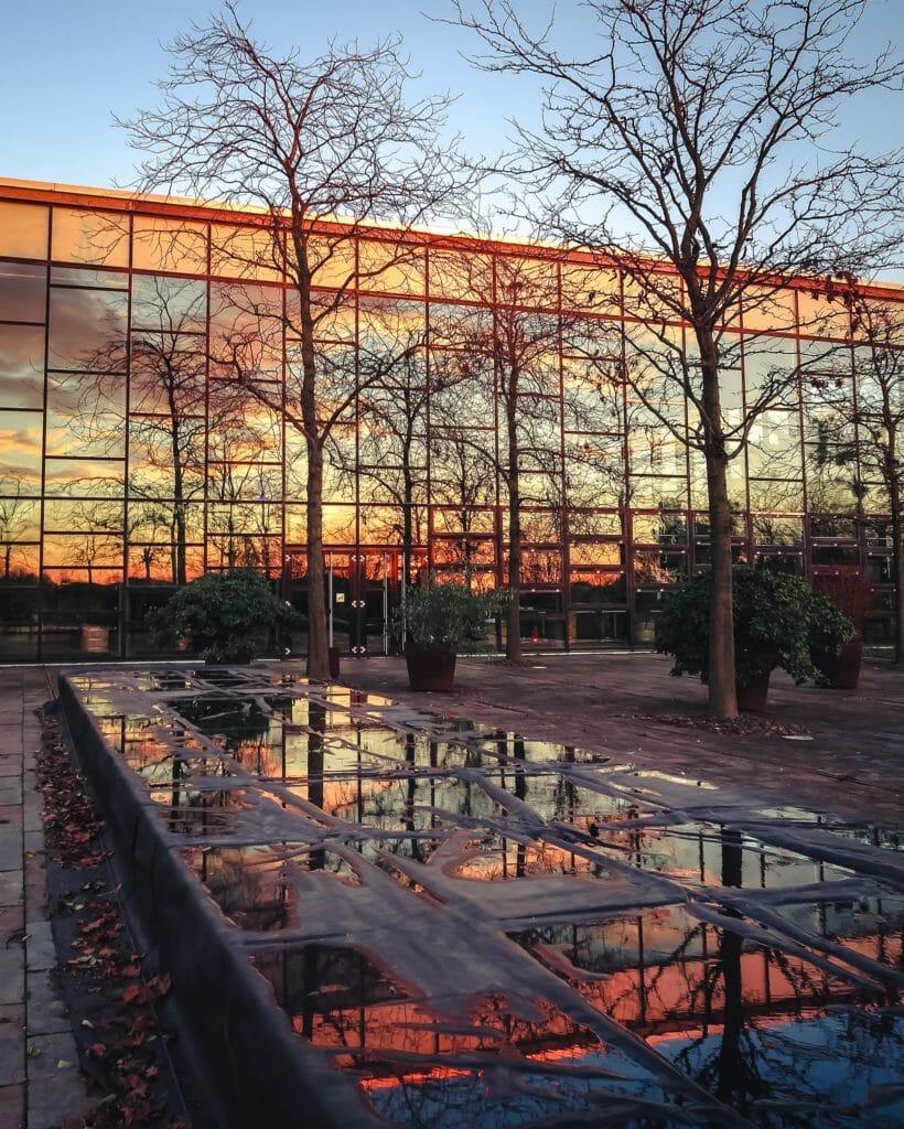 Sonnenuntergang bei der Biosphäre in Potsdam. Das rote Licht der Sonne spiegelt sich in den Glasfronten und auf dem Brunnen.